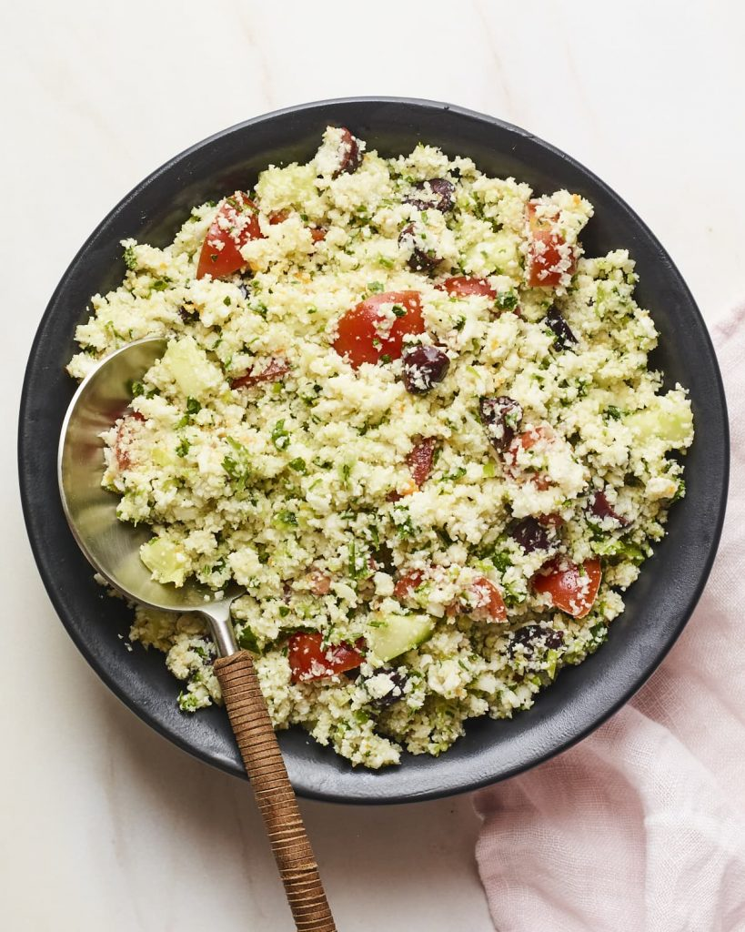 Serving bowl of cauliflower tabbouleh with a serving spoon.